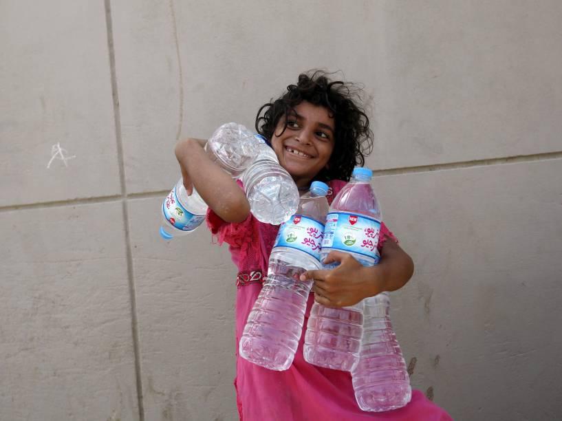 Garota carrega garrafas cheias de água coletadas de uma distribuição de caridade durante uma onda de calor em Carachi, Paquistão, durante o mês do Ramadã
