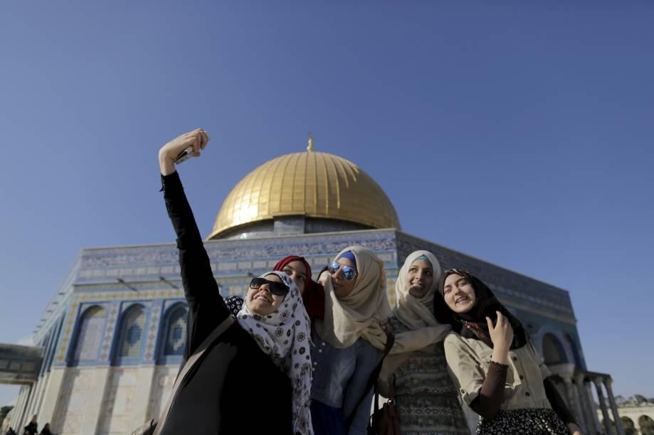 Mulheres palestinas tiram selfies em frente ao Domo da Rocha, santuário localizado em Jerusalém, durante o Ramadã