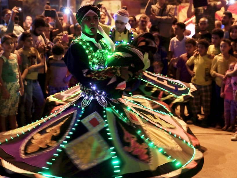 Crianças assistem um dervixe rodopiar enquanto apresenta uma dança tradicional durante as celebrações do Ramadã, no Cairo, Egito