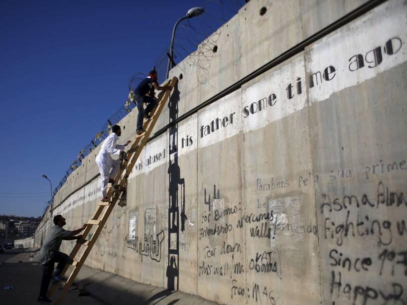 Palestinos impedidos de chegar a Jerusalém pelas forças de segurança israelenses usam uma escada para subir uma controversa barreira feita por Israel, enquanto tentam participar da quarta reza de sexta-feira do Ramadan, na vila de Al-Ram