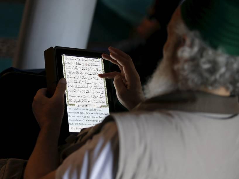 Muçulmano lê o Alcorão em árabe e alemão em seu tablet durante as rezas de sexta-feira em uma mesquita em Berlin, Alemanha