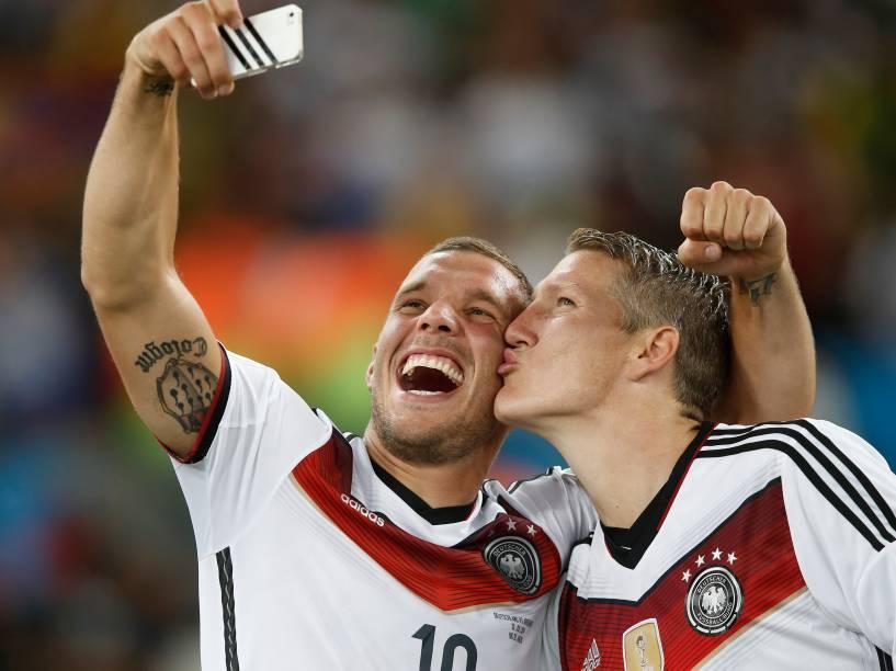Os jogadores Bastian Schweinsteiger e Lukas Podolski tiram selfie após a Alemanha vencera Copa do Mundo realizada no Brasil