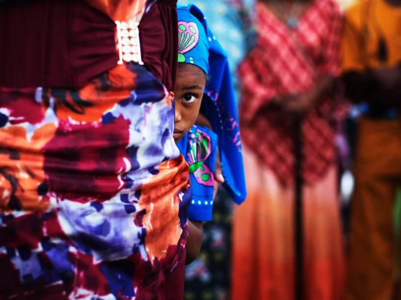 Menina de uma comunidade africana popularmente conhecida como The Black Hebreus, se esconde durante uma celebração na cidade de Dimona, em Israel