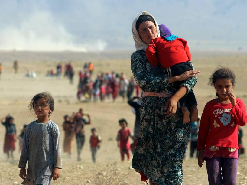 Integrantes da minoria yazidi percorrem dezenas de quilômetros a pé pelo deserto rumo à Síria, depois de escaparem de região cercada pelo Estado Islâmico no Iraque