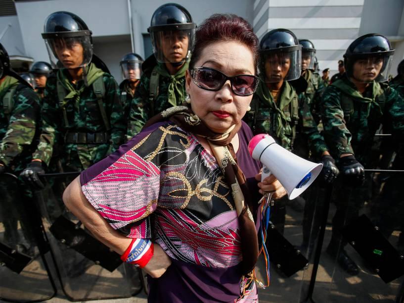Manifestante contra o governo passa por soldados tailandeses em frente ao Ministério da Defesa. O regime militar assumiu o governo depois de um golpe de Estado, em maio