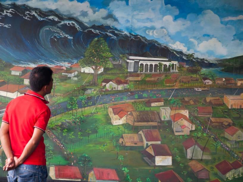 Sobrevivente observa pintura que retrata o desastre natural durante uma exposição em Lambada, na Indonésia