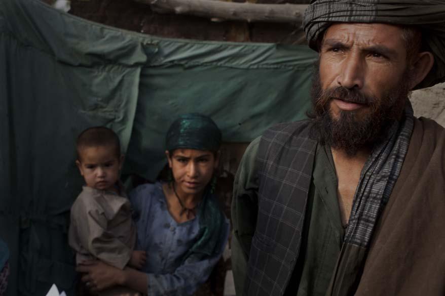 Habitantes afegãos esperam para serem revistado por soldados americanos na vila de Kuhak