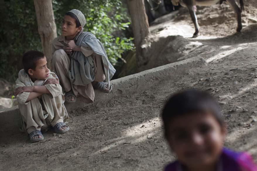 Crianças escutam conversa entre um soldado americano e um afegão
