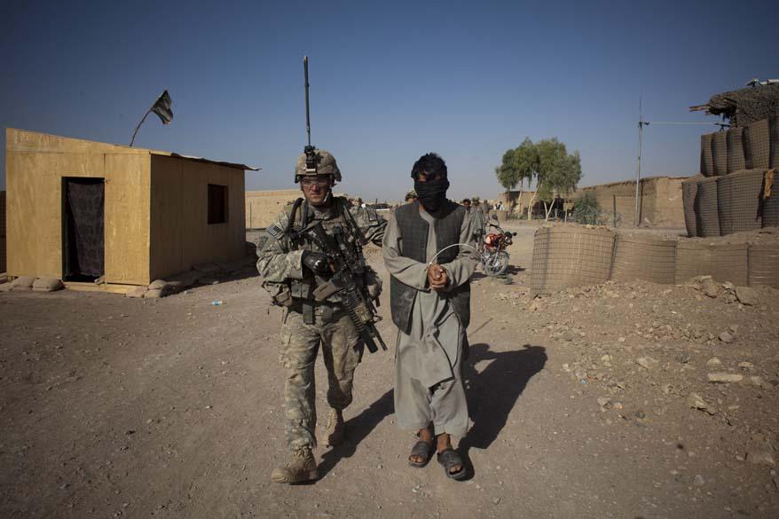 Um rebelde suspeito é levado para posto de combate americano por um soldado americano
