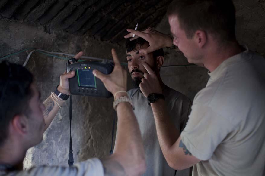 Um suspeito talibã é submetido a testes biométricos aplicados por soldados americanos