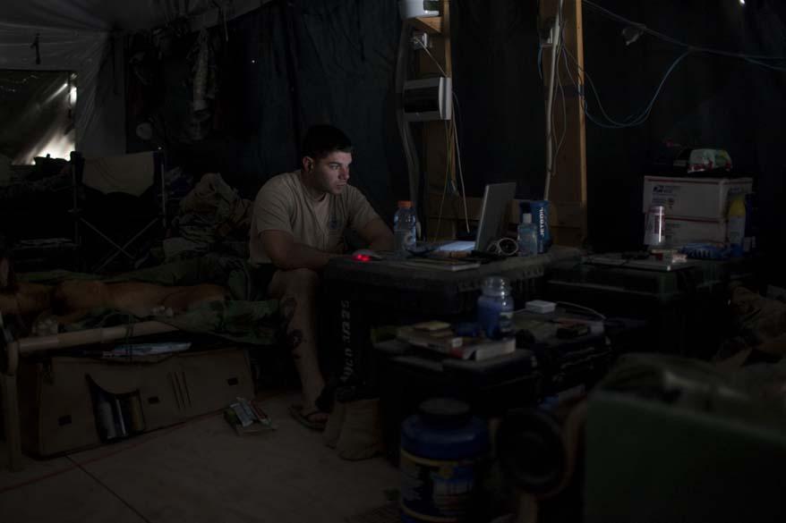 Soldado americano assiste a um filme em seu computador em barraca militar