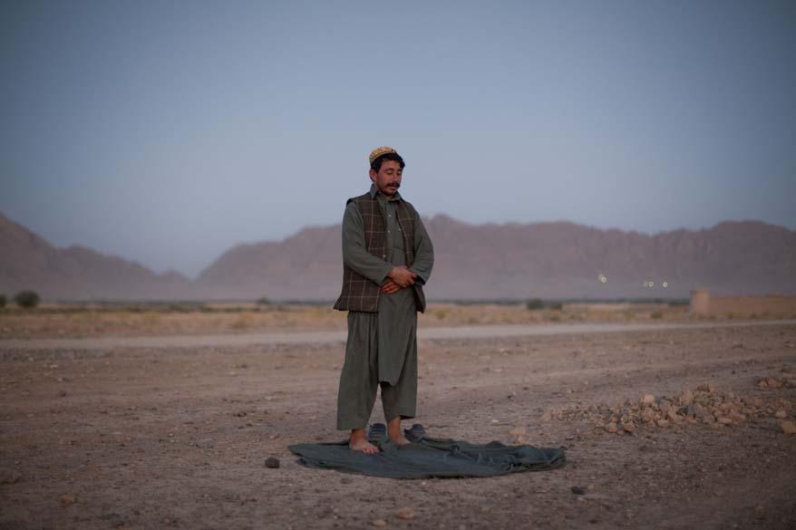 Chefe de polícia local reza durante o anoitecer em Arghandab