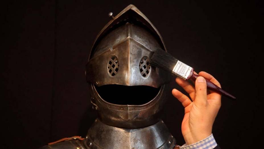 Funcionário limpa armadura de 1580 durante os preparativos para a Olympia International Fine Art and Antiques Fair, feira de artes e antiguidades que abre amanhã em Londres