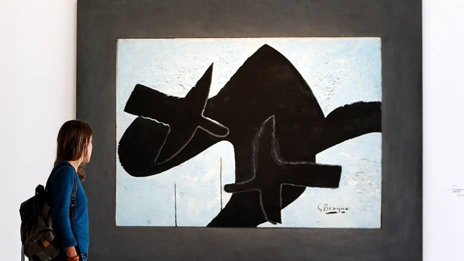 """Visitante olha para a pintura """"Les oiseaux noirs"""" (Os pássaros pretos, 1956-1957), do pintor francês Georges Braque (1882-1963), durante exposição no Museu do Grand Palais em Paris"""