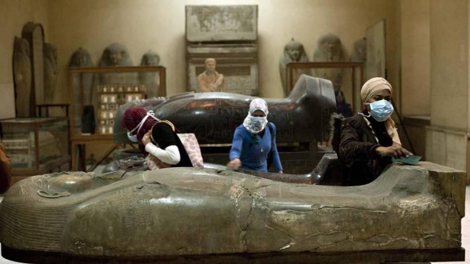 Mulheres limpam artefatos históricos no Museu Egípcio, Cairo