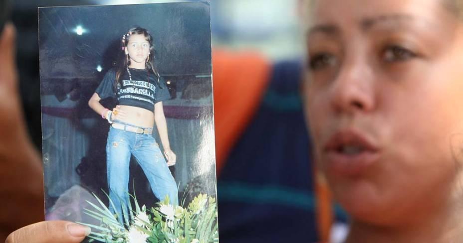 Mulher em frente a um hospital no Rio de Janeiro mostra foto da jovem Larissa dos Santos Atanázio, uma das vítimas da tragédia na Escola Municipal Tasso da Silveira, no bairro Realengo, Rio de Janeiro