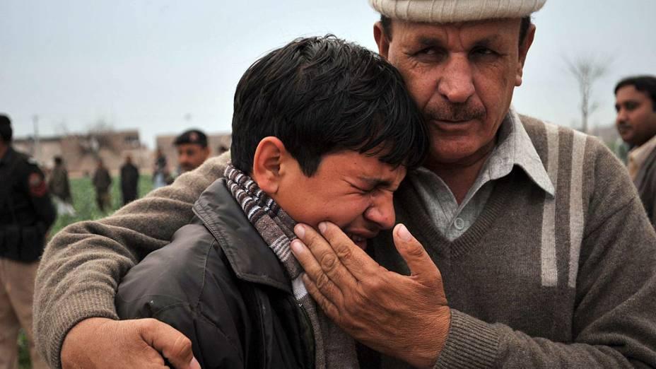 Homem conforta filho de militante islâmico morto em ataque suicida na fronteira de Peshawar, Paquistão