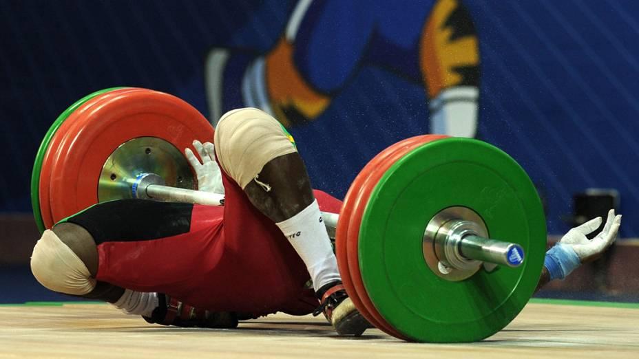 O atleta ganense Seth Degbe Fetrie cai durante prova de levantamento de peso nos Jogos da Comunidade Britânica, em Nova Deli, Índia
