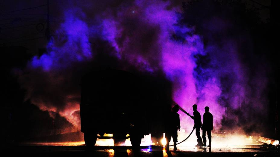 Bombeiros paquistaneses trabalham em um veículo em chamas depois de ter sido incendiado por manifestantes em protesto contra homicídios cometidos em seu distrito, em Karach