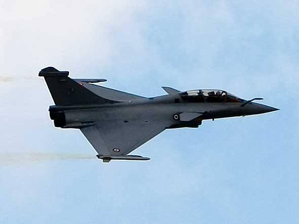 Um Rafale, da Dassault, voa sobre Paris. Esse caça pode carregar uma variedade de armamentos sob as asas e conta com sistemas eletrônicos avançados para dificultar sua detecção pelo radar