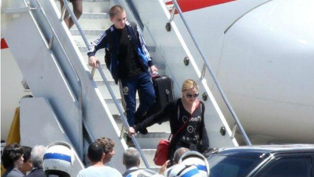Madonna e o filho Rocco descem do avião, carregando as próprias malas