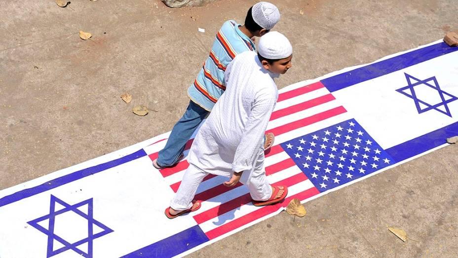 Garotos Muçulmanos caminham sobre as bandeiras de Israel e Estados Unidos durante a manifestação anti-Israel em Hyderabad, na Índia
