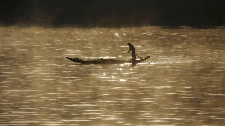 Homem pesca no rio Xinan na província de Anhui, na China