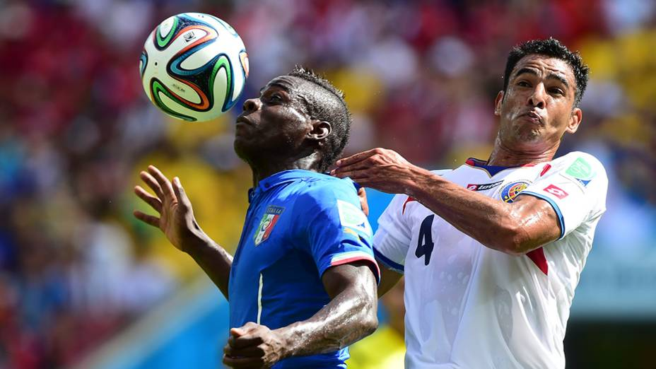 Balotelli, da Itália, disputa a bola com Umaña, da Costa Rica, na Arena Pernambuco em Recife
