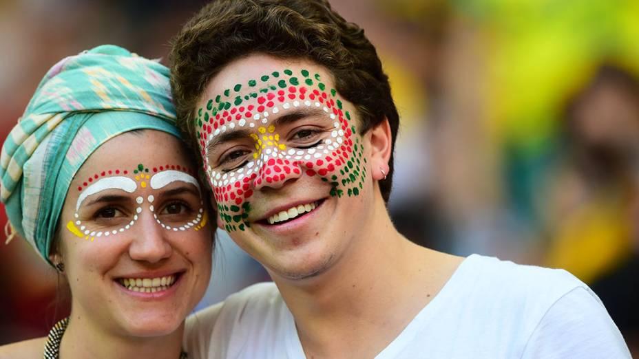 Torcedores pintam o rosto com as cores da bandeira de Gana