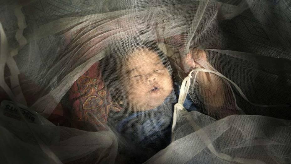 Bebe vítima das inundações nas Filipinas descansa em uma escola de Manila