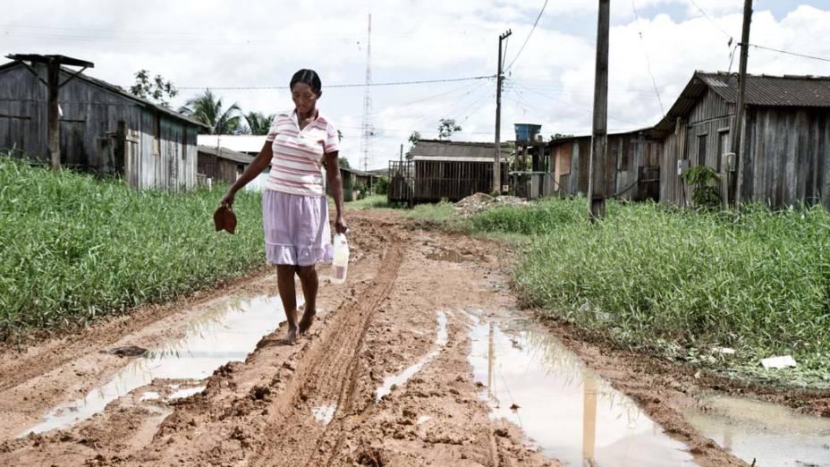 Maria Nazaré do Nascimento poupa os sapatos e suja os pés na rua sem asfalto e repleta de lama do bairro Boa Esperança, em Altamira