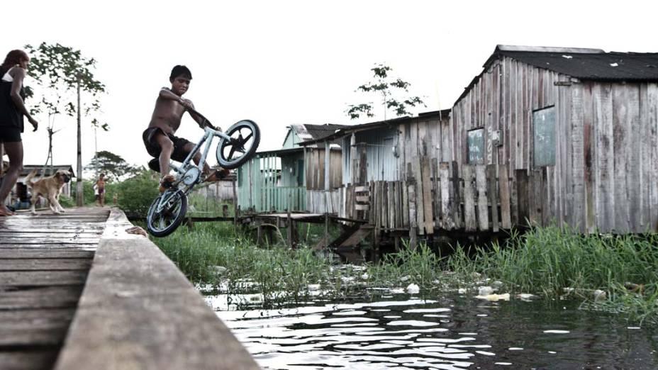 A diversão do menino é mergulhar na água suja do igarapé que corre embaixo de casa. As doenças de pele castigam as crianças de Altamira