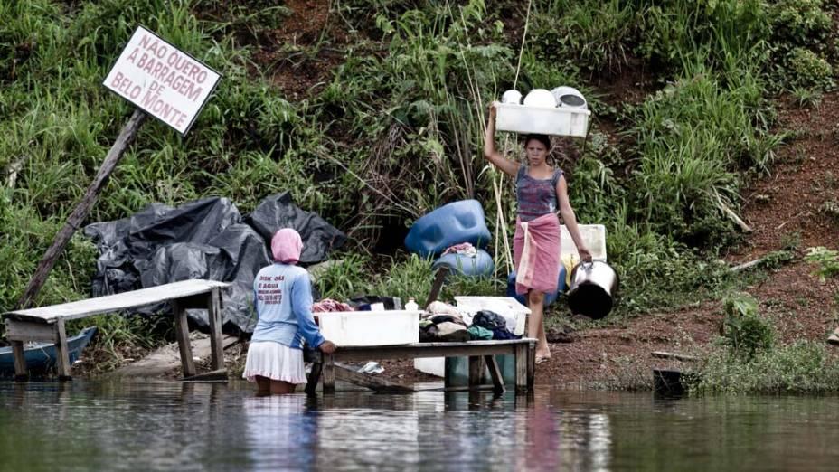 Rosilene Costa Silva (de costas) e Adriele da Silva Balão usam a água do Xingu para lavar roupas ao lado de placa contra Belo Monte. Com as obras, casas serão removidas