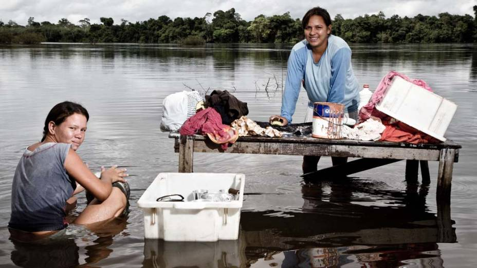 """Rosilene Costa Silva, de 27 anos, e a cunhada, Adriele Silva Balão, de 17, lavam roupa à beira do Xingu. Terão que sair da casa onde moram: """"Meu marido diz que não sabe fazer outra coisa a não ser pescar"""", diz Rosilene"""