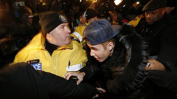 Cercado por policiais e seguranças, Justin Bieber chega à delegacia em Toronto