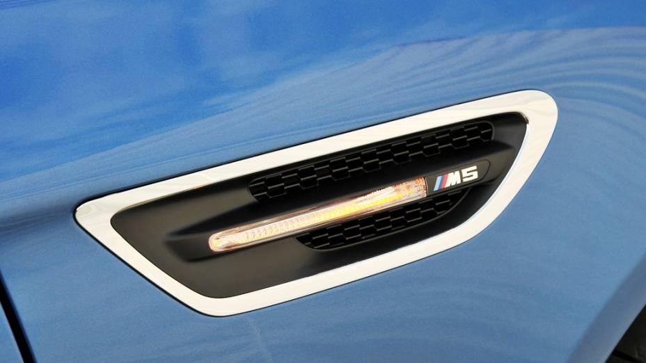 Entre os detalhes visuais do M5 está a saída de ar lateral emoldurada, e que traz a barra da luz do pisca ao centro, com o emblema do M5 na ponta da peça