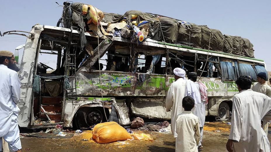 Paquistaneses observam nesta segunda-feira restos de ônibus alvo de bomba ativada por controle remoto em Mastung, no Paquistão. Pelo menos seis pessoas morreram e cerca de 50 ficaram feridas