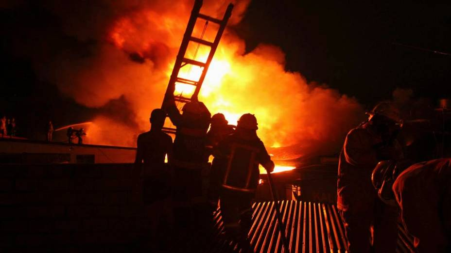 Bombeiros durante combate à incêndio em armazém de roupas e tecidos em Manila, Filipinas
