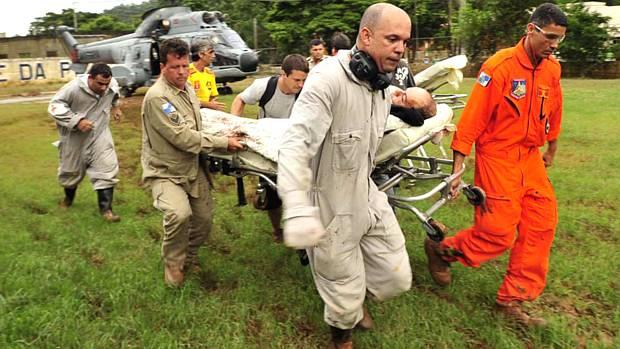 Bombeiros carregam sobrevivente socorrido em Teresópolis, na quarta-feira