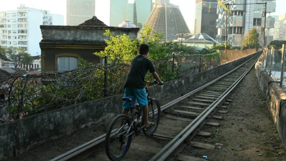 Um menino anda de bicicleta sobre os trilhos, próximo aos Arcos da Lapa
