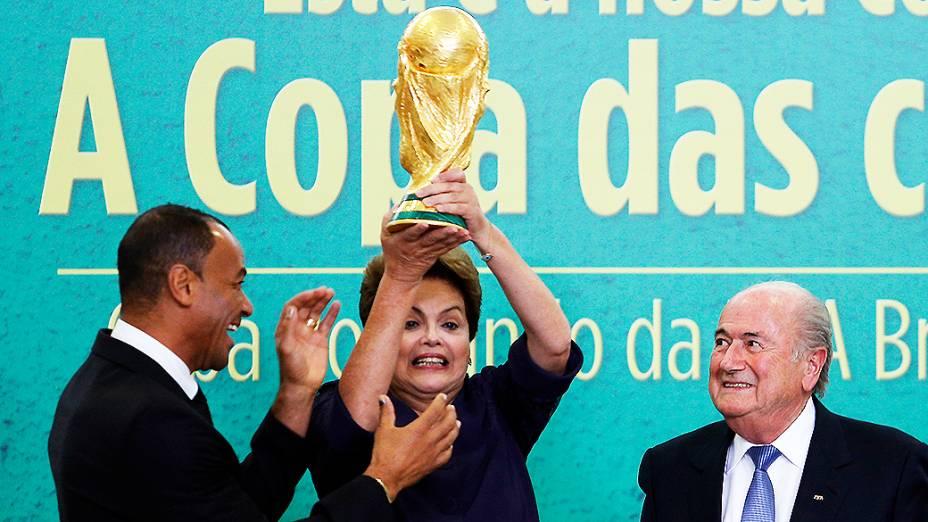 Presidente Dilma Rousseff levanta a Taça da Copa do Mundo nesta segunda-feira (2), durante apresentação oficial pelo presidente da Fifa, Joseph Blatter, no Palácio do Planalto em Brasília
