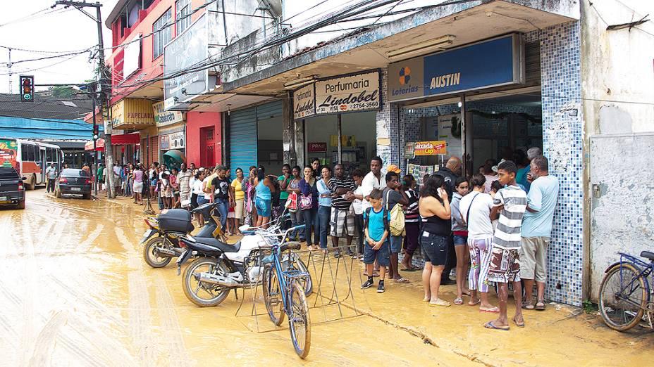 Pessoas formam fila em uma lotérica em Nova Iguaçu, após fortes chuvas atingirem o Rio de Janeiro