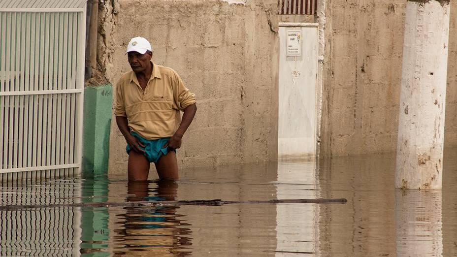 Homem atravessa rua alagada no bairro de Nova Itaparica, no Espírito Santo