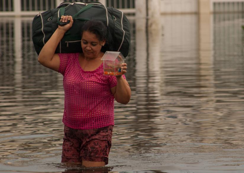 Mulher atravessa rua alagada no bairro de Nova Itaparica, no Espírito Santo
