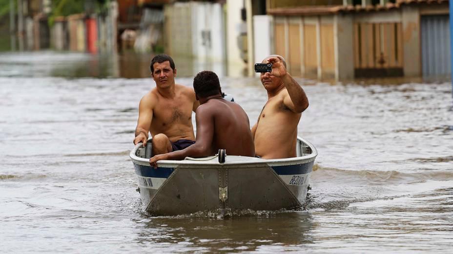 Pessoas atravessam rua de barco devido ao transbordamento de rios causado pelas fortes chuvas no municipio de Serra, próximo a Vitória, Espírito Santo