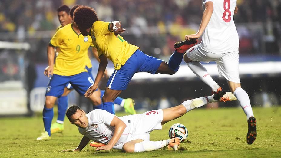 Jogador da Sérvia dá um carrinho em William, durante amistoso no estádio do Morumbi em São Paulo