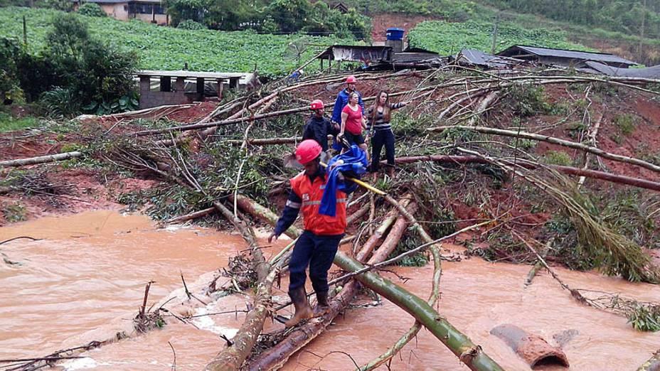Imagem cedida pela prefeitura de Santa Maria de Jetibá, no Espírito Santo, mostra uma equipe da Defesa Civil ajudando uma família a fugir das inundações provocadas pelas fortes chuvas que atingem o estado