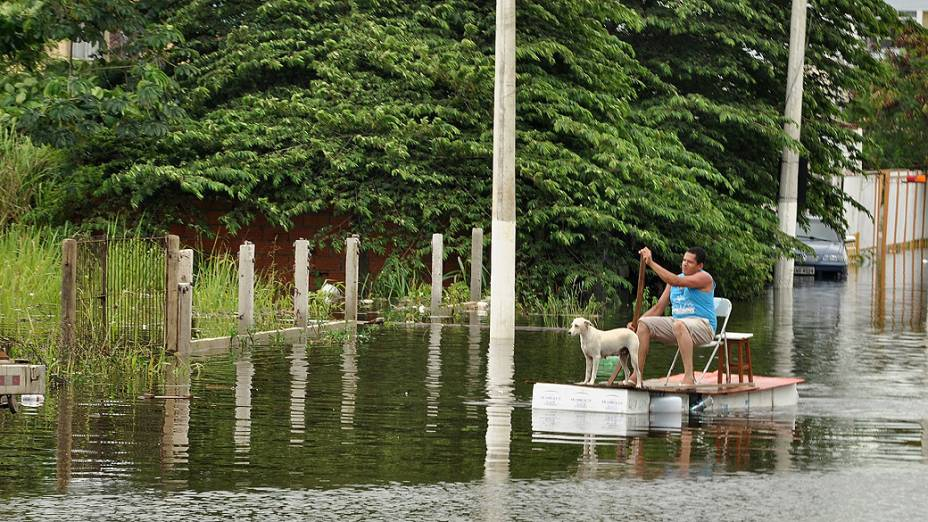 Imagem cedida pela prefeitura de Vila Velha, mostra um homem em uma embarcação improvisada pelas ruas inundadas do Jardim Garanhuns, afetadas pelas fortes chuvas que atingem estado do Espírito Santo