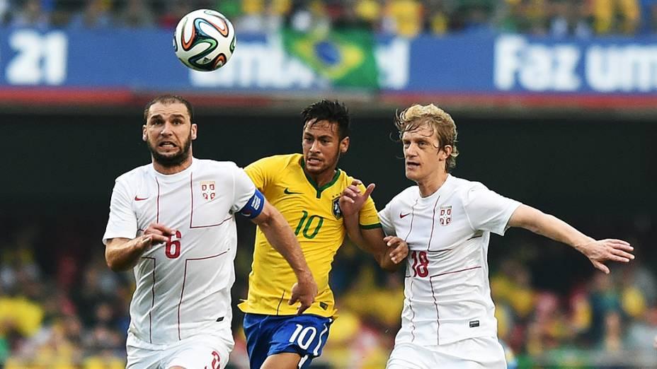 Neymar disputa a bola com dois jogadores da Sérvia, em São Paulo