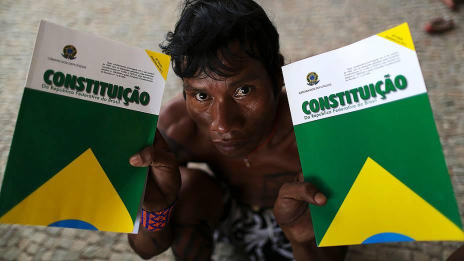 Indígena segura dois livretos da Constituição, no Palácio do Planalto, durante protesto contra a demarcação de terras indígenas e reservas no Brasil